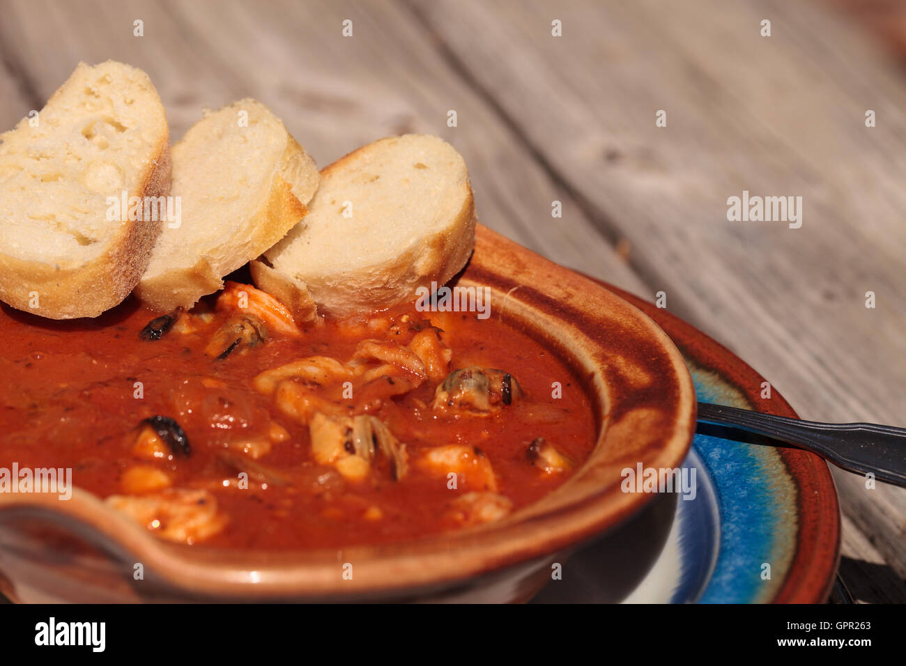 Seafood cioppino with French bread and shrimp, fish, clams ...