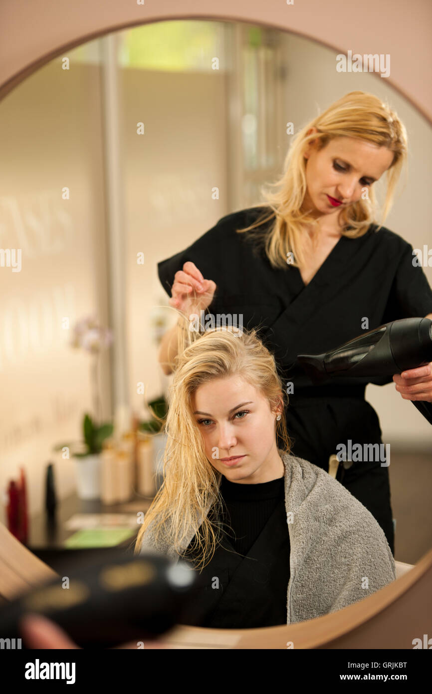 professional hair stylist at work hairdresser doing hairstyle to beautiful young blonde customer in a professional studio - Professional Hair Stylist