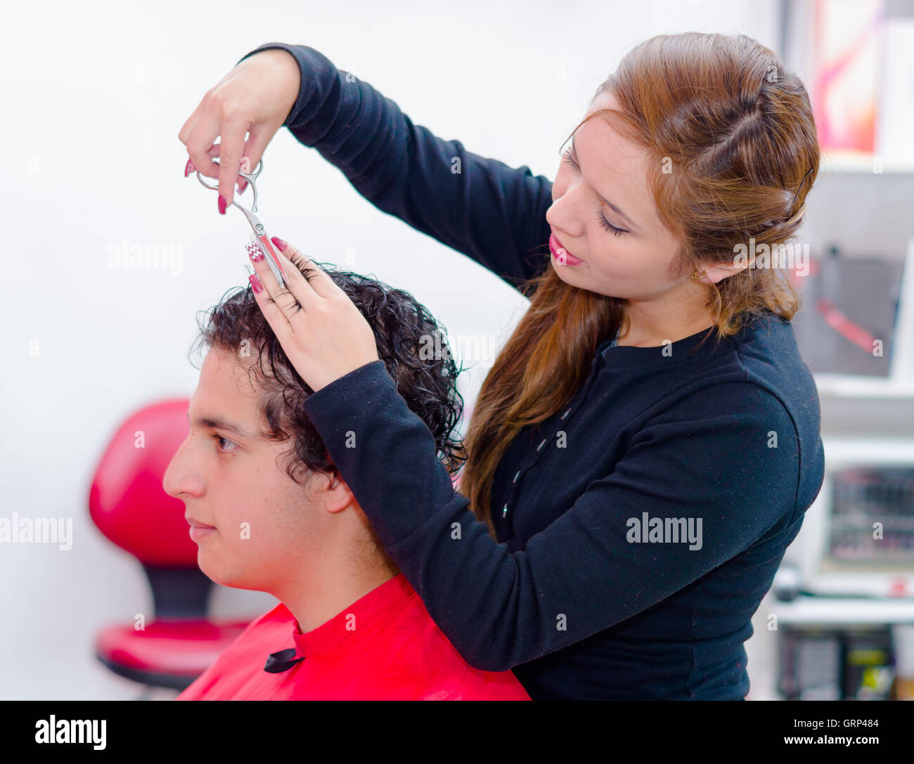 professional hairstylist is cutting a curly man hair with scissors