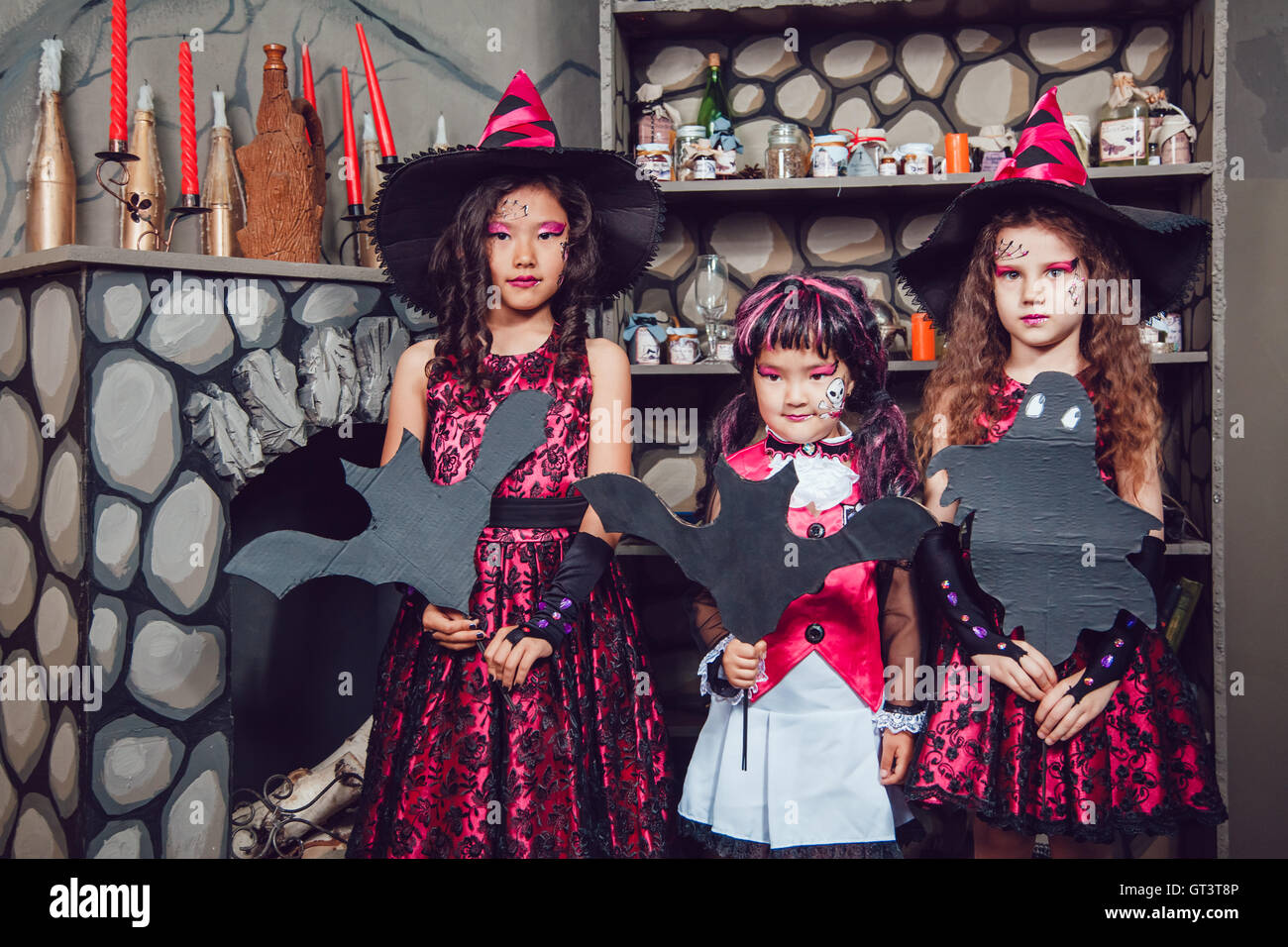 stock photo three girls in witch costumes are in halloween decorations - Halloween Costumes Three Girls
