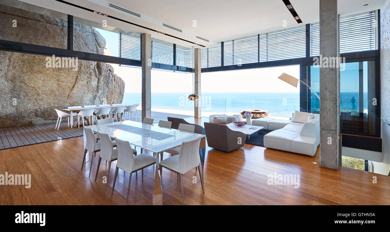modern luxury living room and dining room open to patio with ocean view