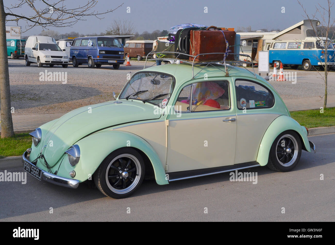 Classi Volkswagen Beetle In Pistachio Green With Retro Luggage Loaded Onto  A Roof Rack