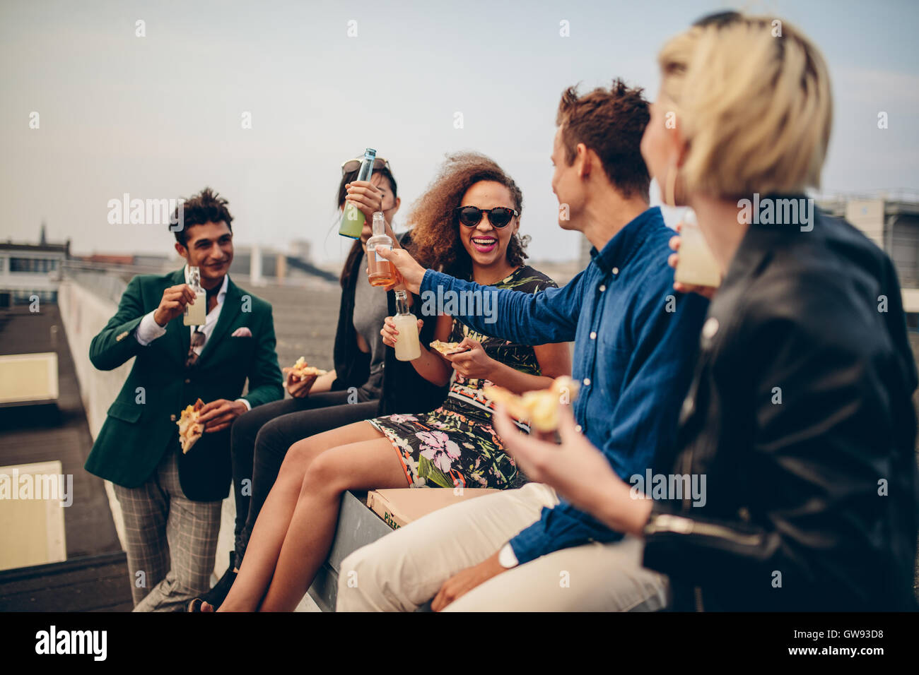 Multiethnic group of young friends partying on terrace for The terrace group