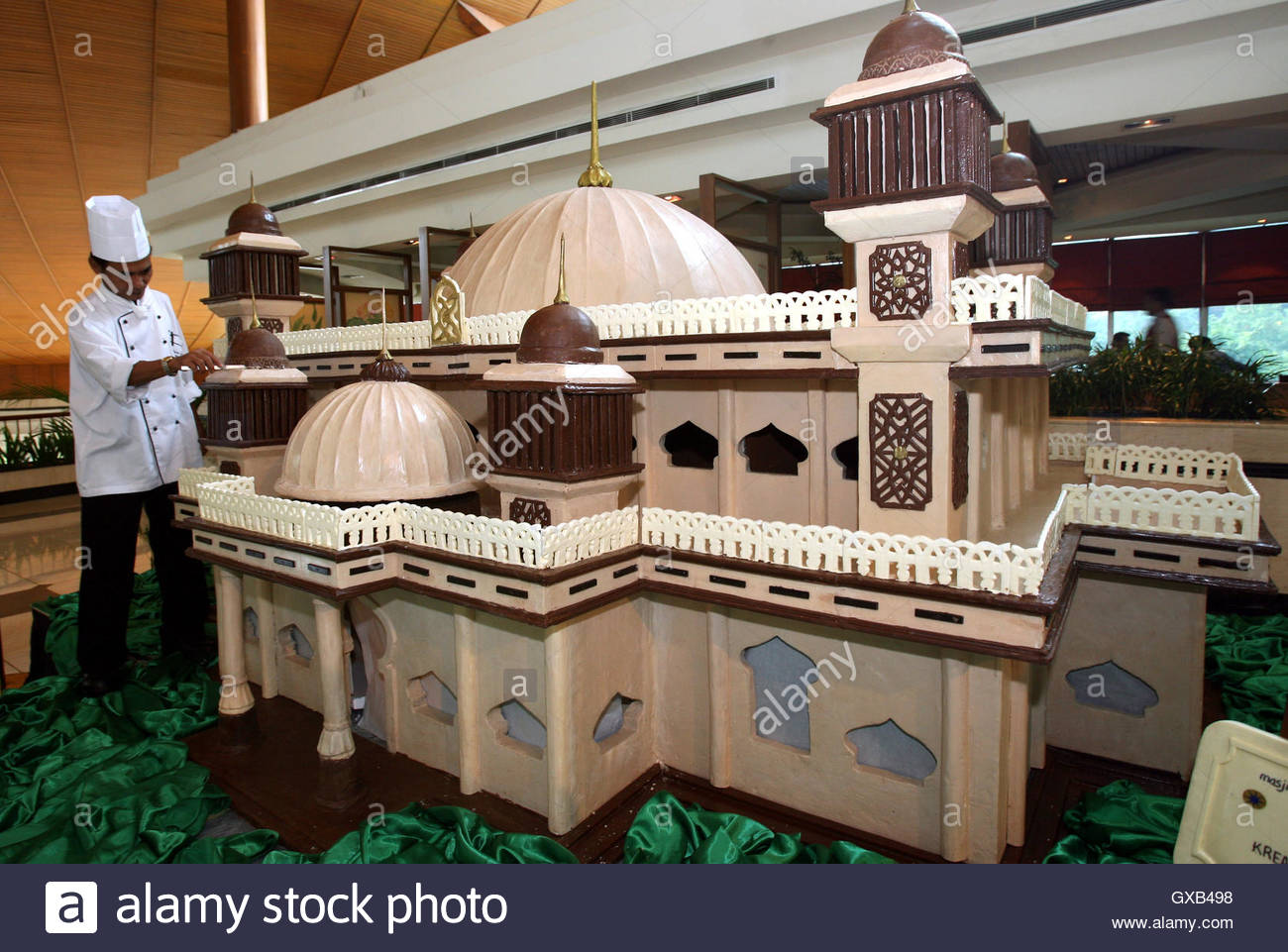 A chef puts finishing touches to a chocolate model of a mosque in ...