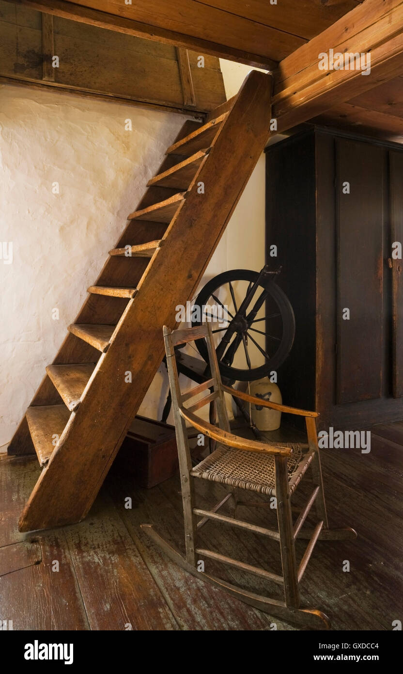Old wooden rocking chair and spinning wheel next to attic stairs in 1785  fieldstone cottage style home Quebec Canada
