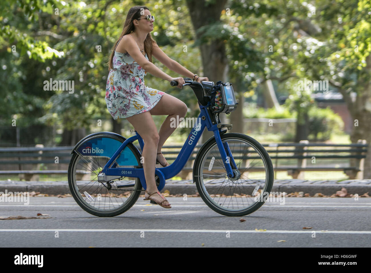 A Young Woman Is Riding A Citibike In Central Park Stock Photo