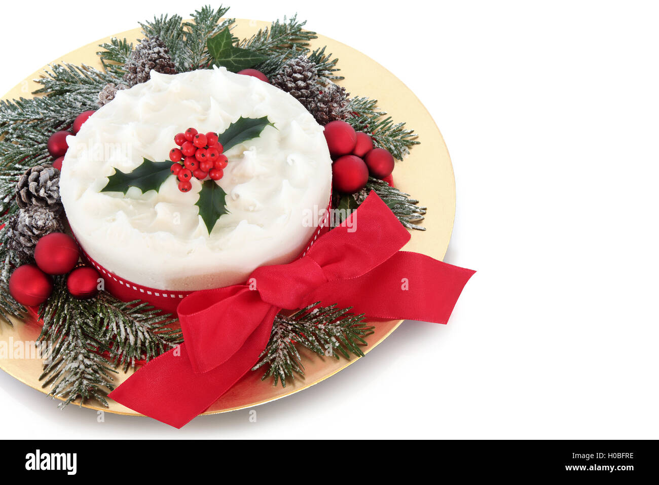 Why is holly a traditional christmas decoration - Stock Photo Traditional Christmas Cake With Red Bauble Decorations Bow Holly And Snow Covered Winter Greenery On A Gold Plate Over White