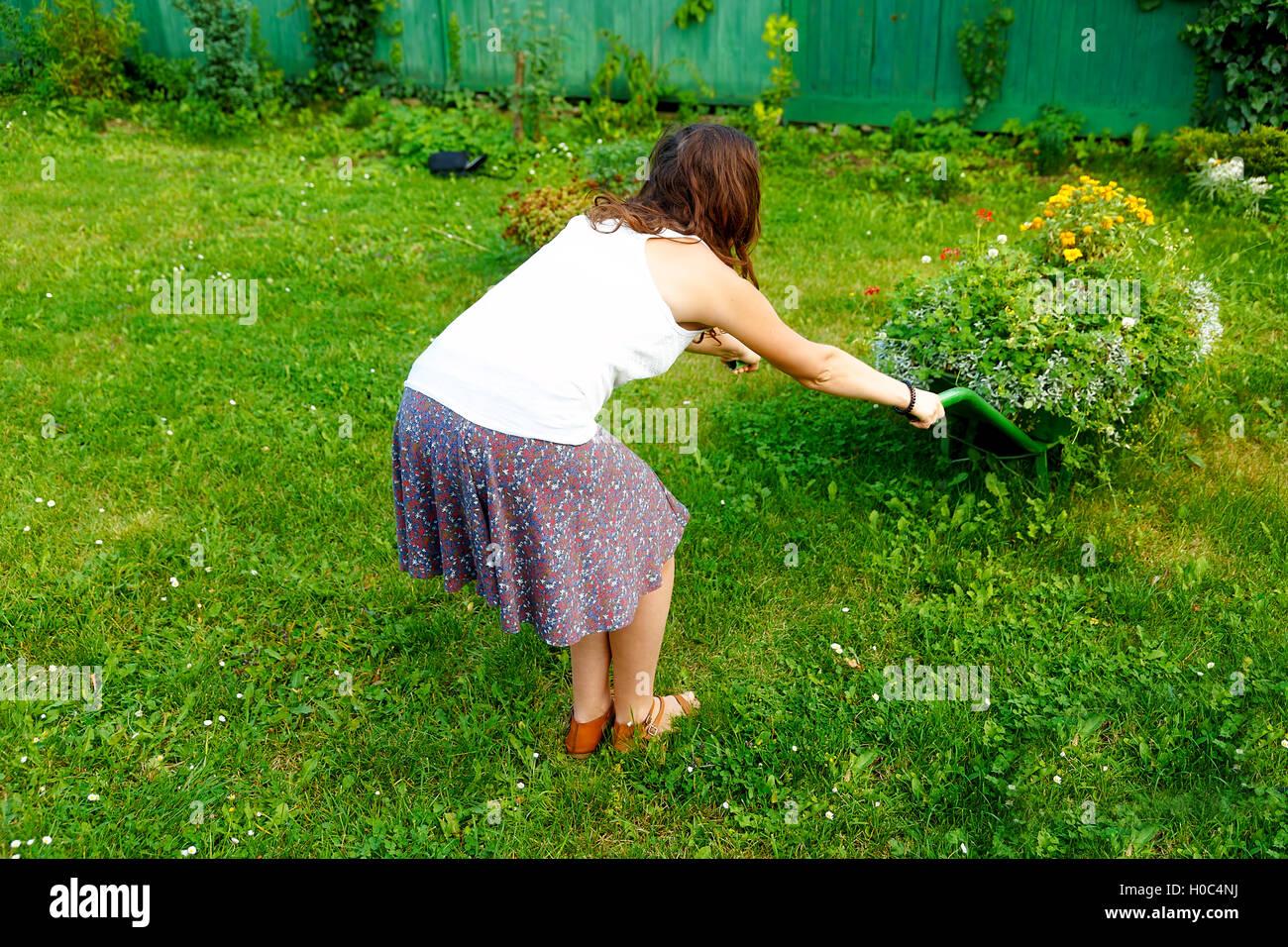 young woman in garden playfully pushing decorative wheelbarrow full ...