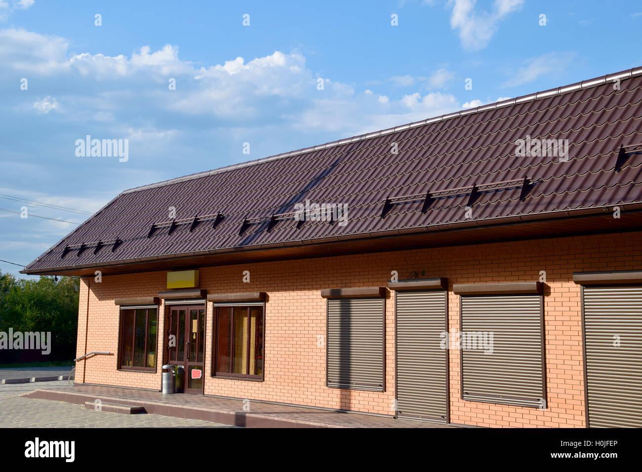 Stock Photo   The Roof Of Corrugated Sheet On A Building. Brown Roofing  Metal Sheets On Rented Store. Brown Shutters On The Windows