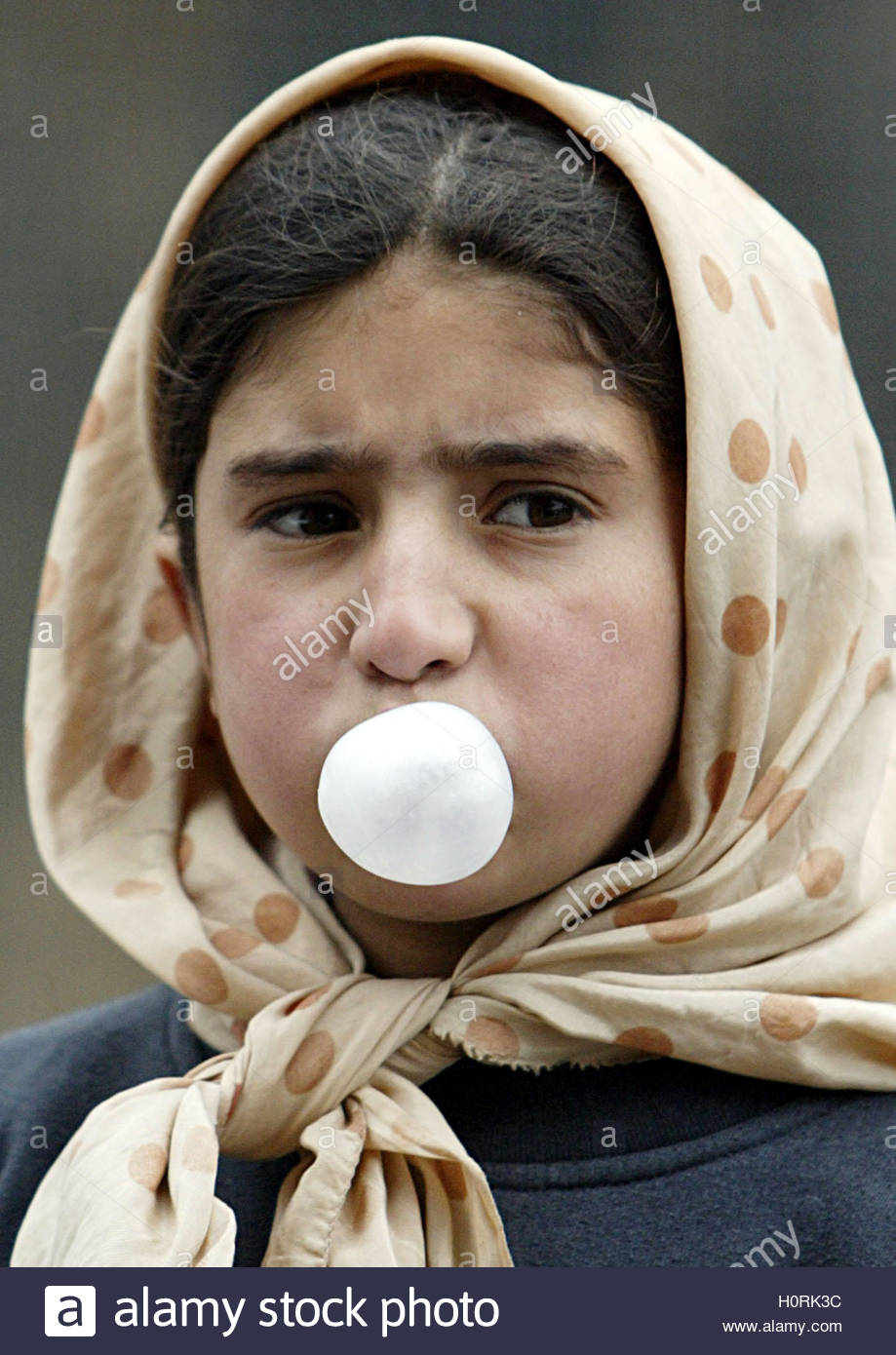 an afghan girl blows a bubble chewing gum in kabul one year after the ousting of the reactionary taliban regime women and girls in continue to face broad restrictions