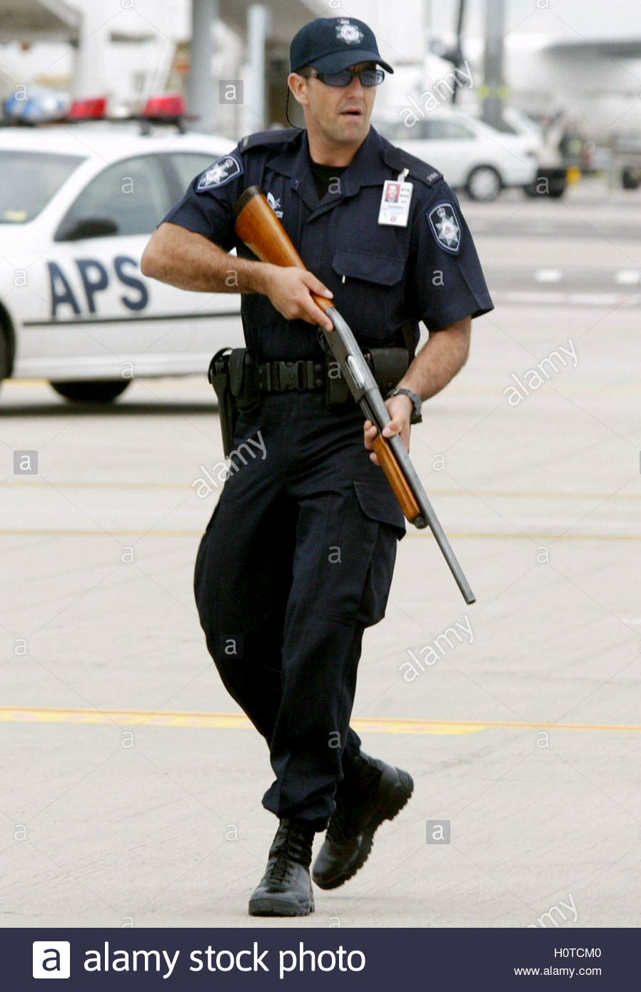 An armed Federal Police officer stands guard as others escort ...