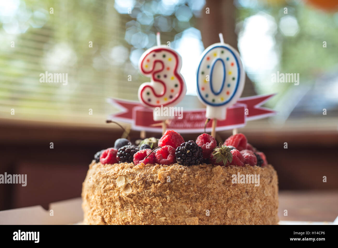 raspberries blackberry birthday cake with candles number 30 Stock