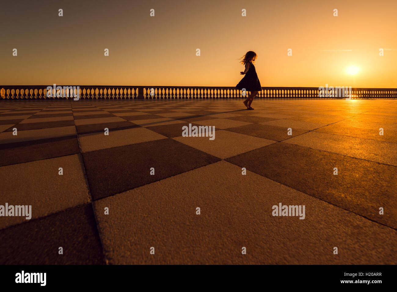 Italy, Livorno, silhouette of little girl dancing on Terrazza ...