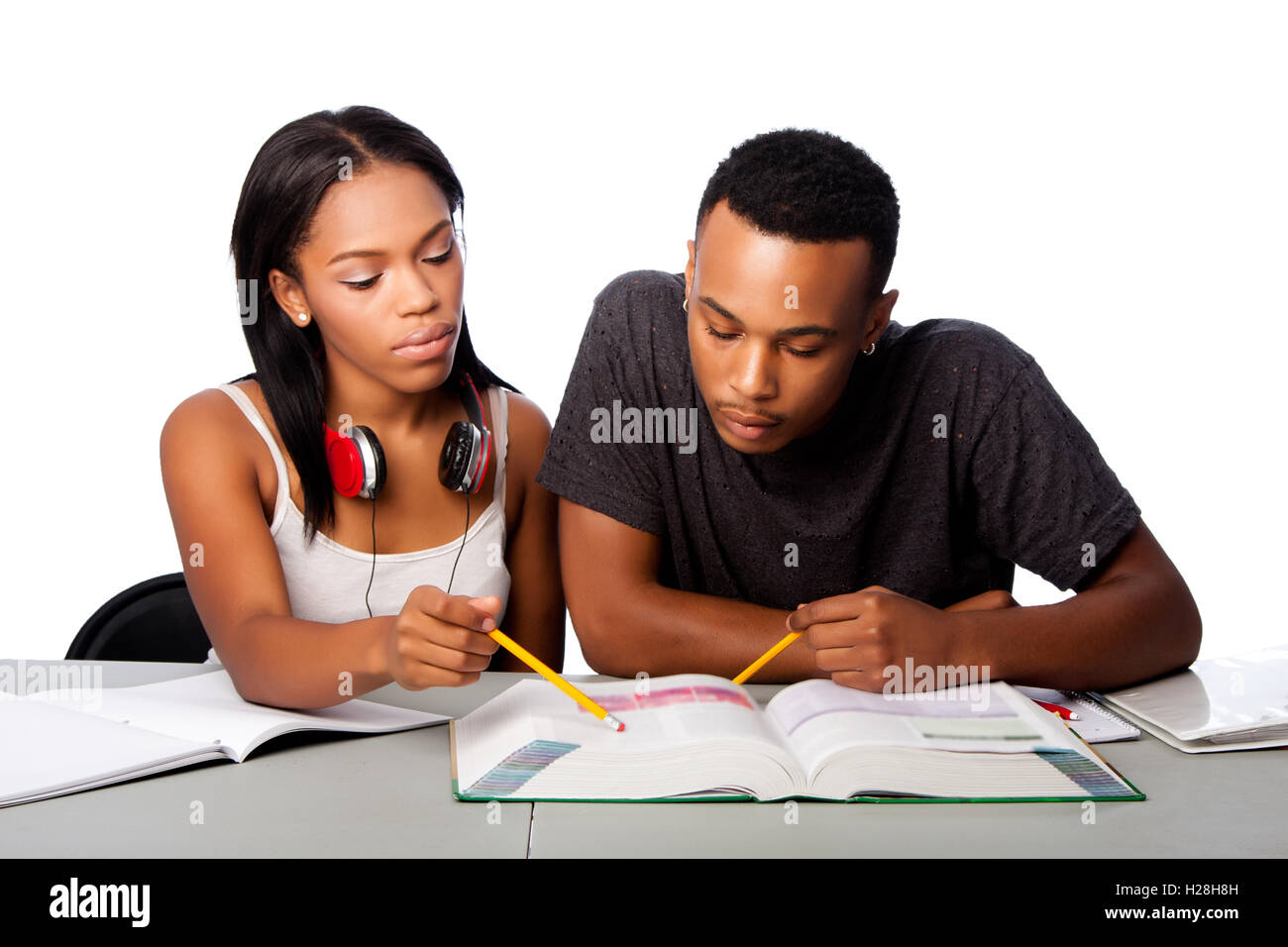 Two students studying together from text book, lifestyle tutoring concept, on white. Stock Photo