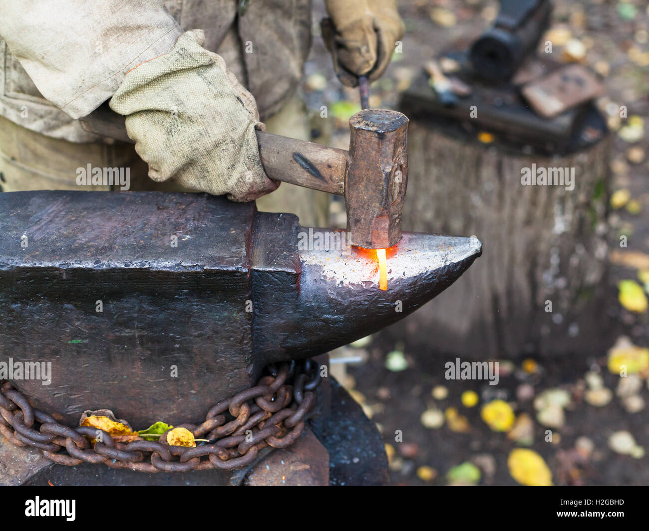 Blacksmith processing red hot iron rod on anvil in outdoor ...
