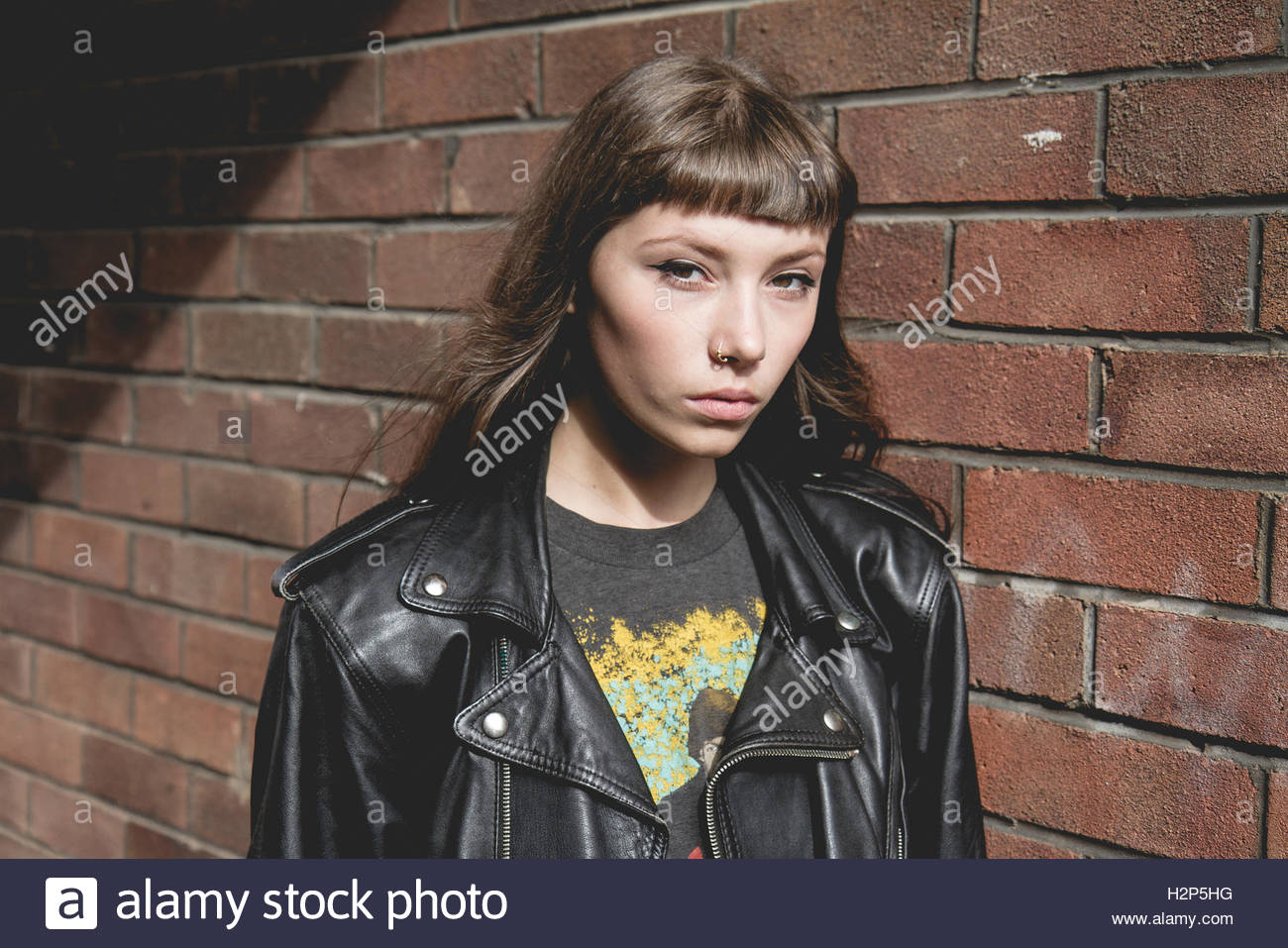 Brunette model with a fringe wears band tee and black leather ...