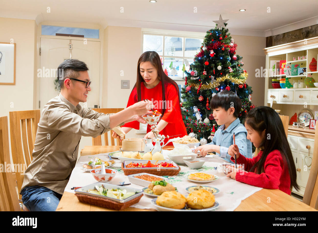 Chinese family enjoying their christmas dinner. They are eating ...