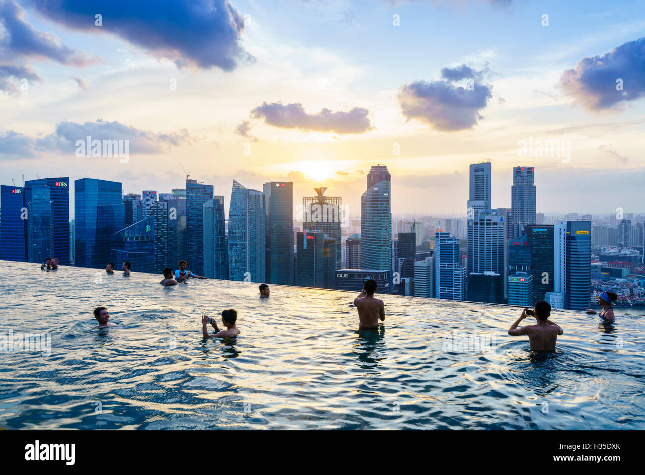 Infinity Pool On The Roof Of Marina Bay Sands Hotel With Spectacular Views Over Singapore Skyline At Sunset