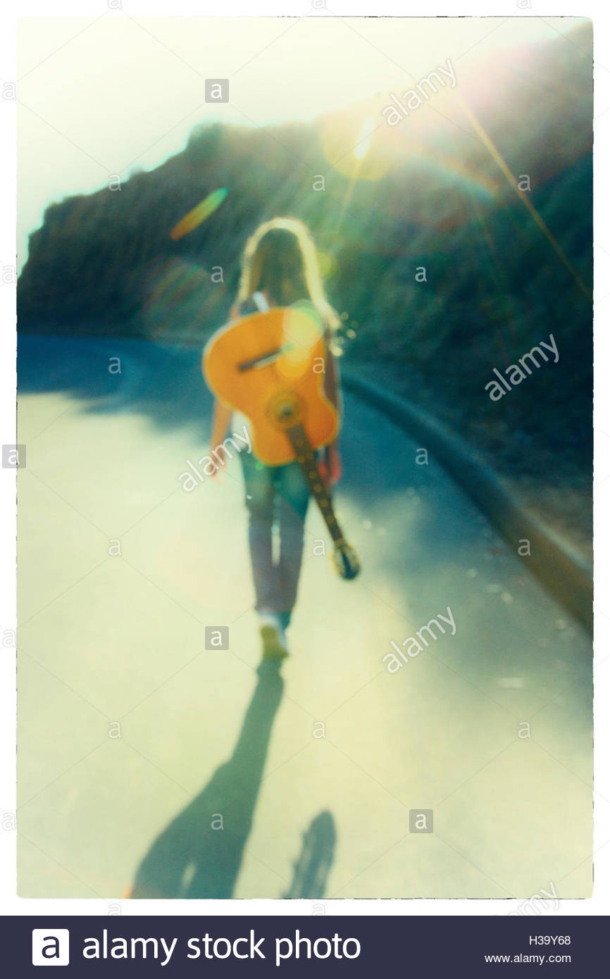 Teenager Walking On A Country Road At Sunset Carrying Guitar Her Back