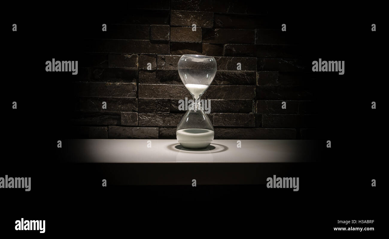 Broken hourglass  Broken hourglass, sand clock on a dark gray brick wall background ...