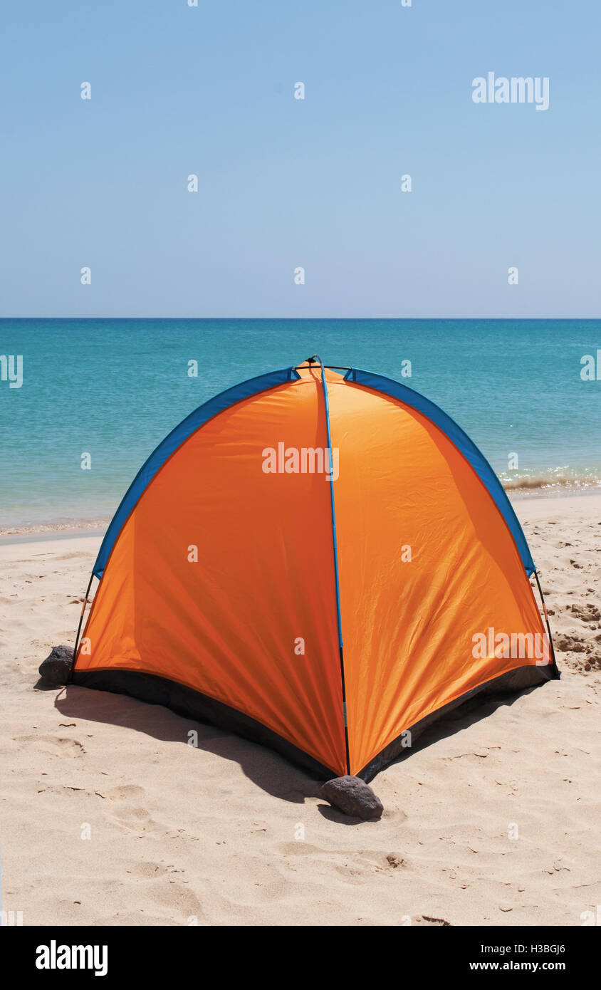 An orange tent on a white beach with crystal clear water on the background & An orange tent on a white beach with crystal clear water on the ...