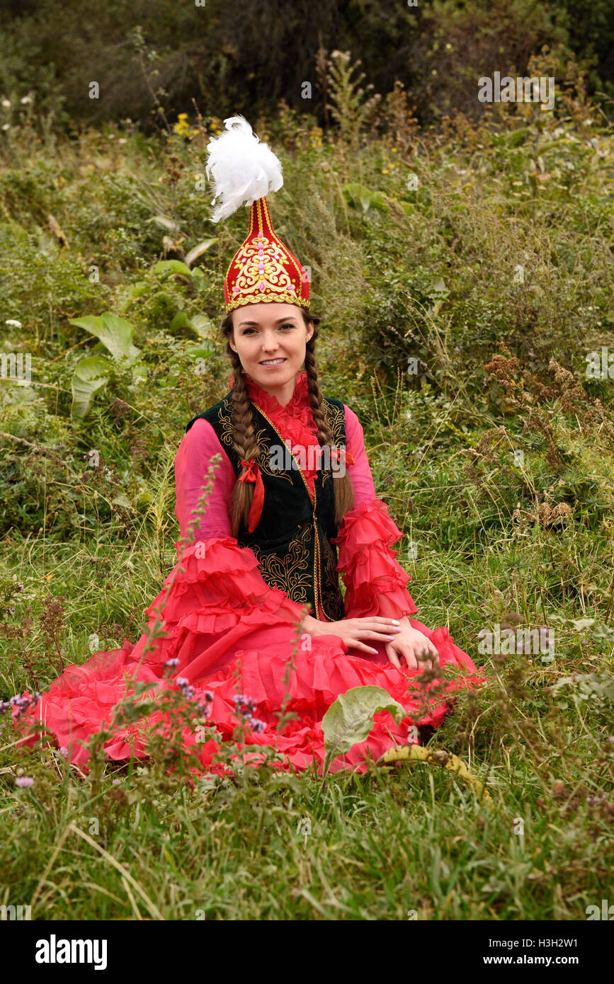 Young Woman In Traditional Kazakh Dress Sitting In A Field