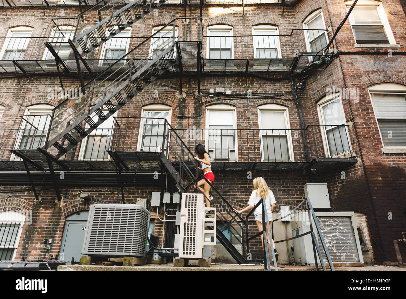 Apartment Building Boston woman climbing fire escape ladder of apartment building, boston