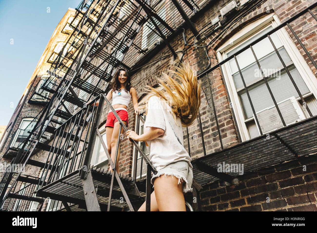 Woman Climbing Fire Escape Ladder Of Apartment Building Boston