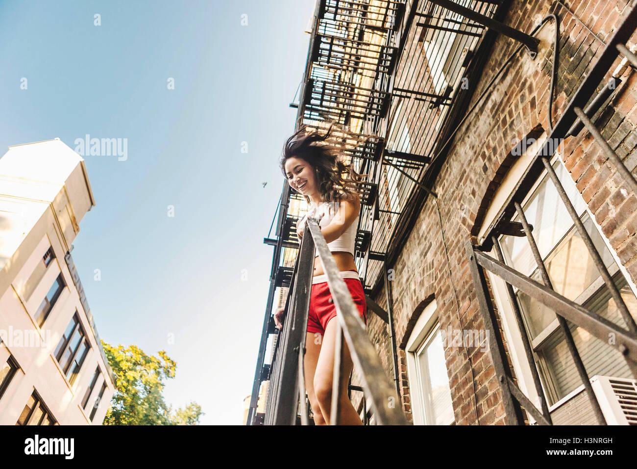 Apartment Building Fire Escape Ladder woman climbing fire escape ladder of apartment building, boston
