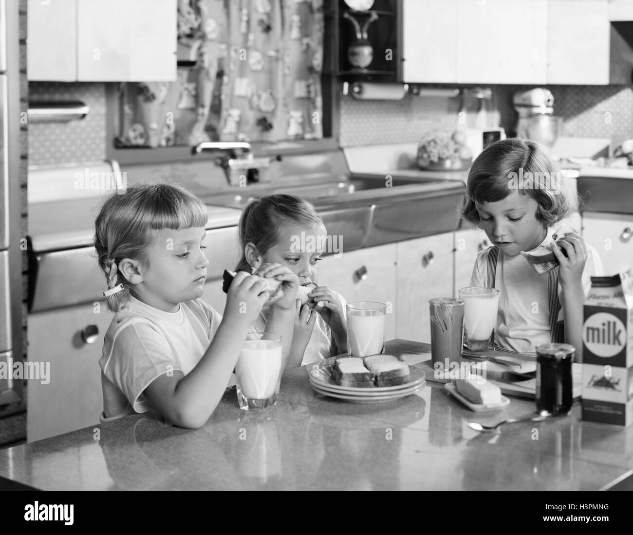1950s three girls sisters eating lunch at kitchen table peanut butter H3PMNG