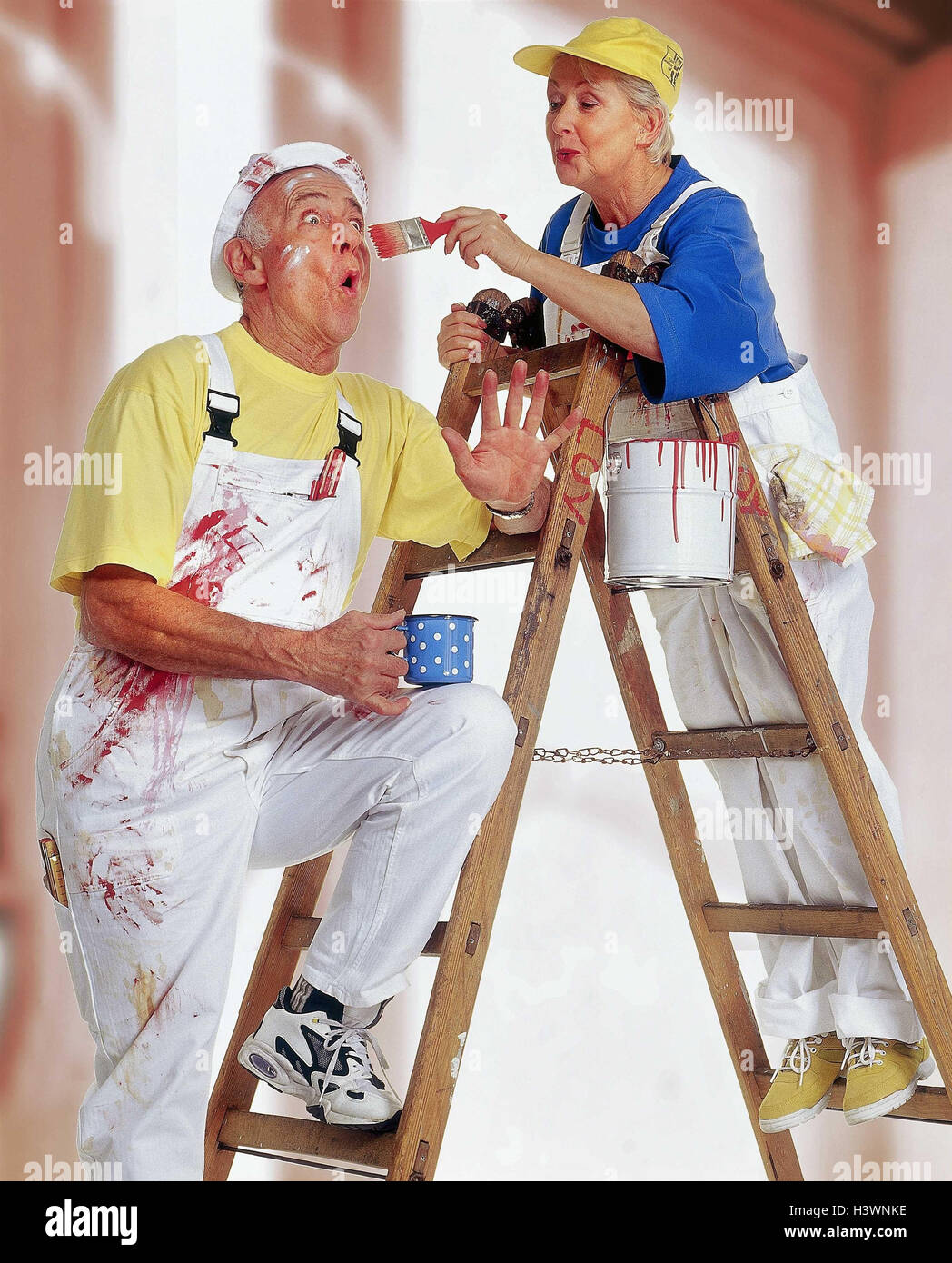 Do it yourself  Senior couple  renovation  colour  conductor  stand  paint   happy  woman  brush  man  look  paint Senior  studio  inside  man  woman   old. Do it yourself  Senior Couple  Renovation  Colour  Conductor