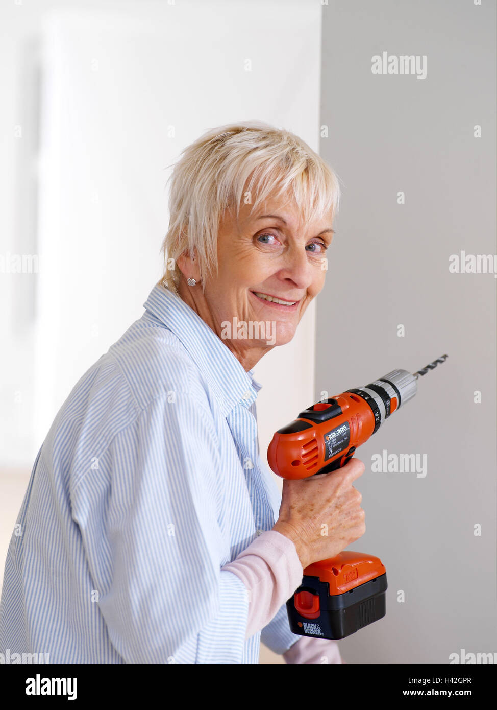 Flat renovation works senior drill smile renovate half flat renovation works senior drill smile renovate half portrait 60 70 years woman pensioner do it yourselfer actively fit agile old person solutioingenieria Gallery