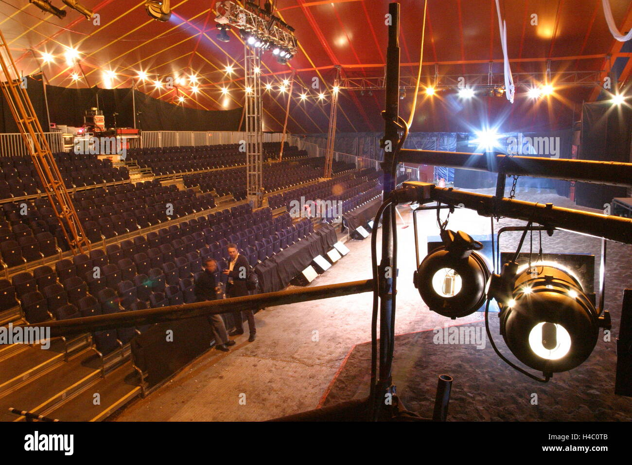 Interior of a newly erected circus-style tent showing sand performance area tiered seating and spotlights in the foreground & Interior of a newly erected circus-style tent showing sand Stock ...