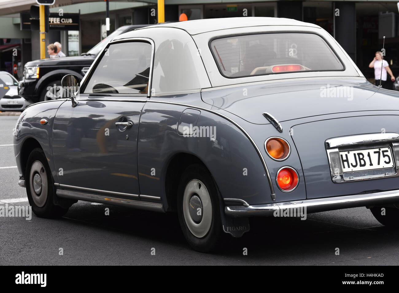 Gray Blue Vintage Car Nissan Figaro At Intersection Stock Photo