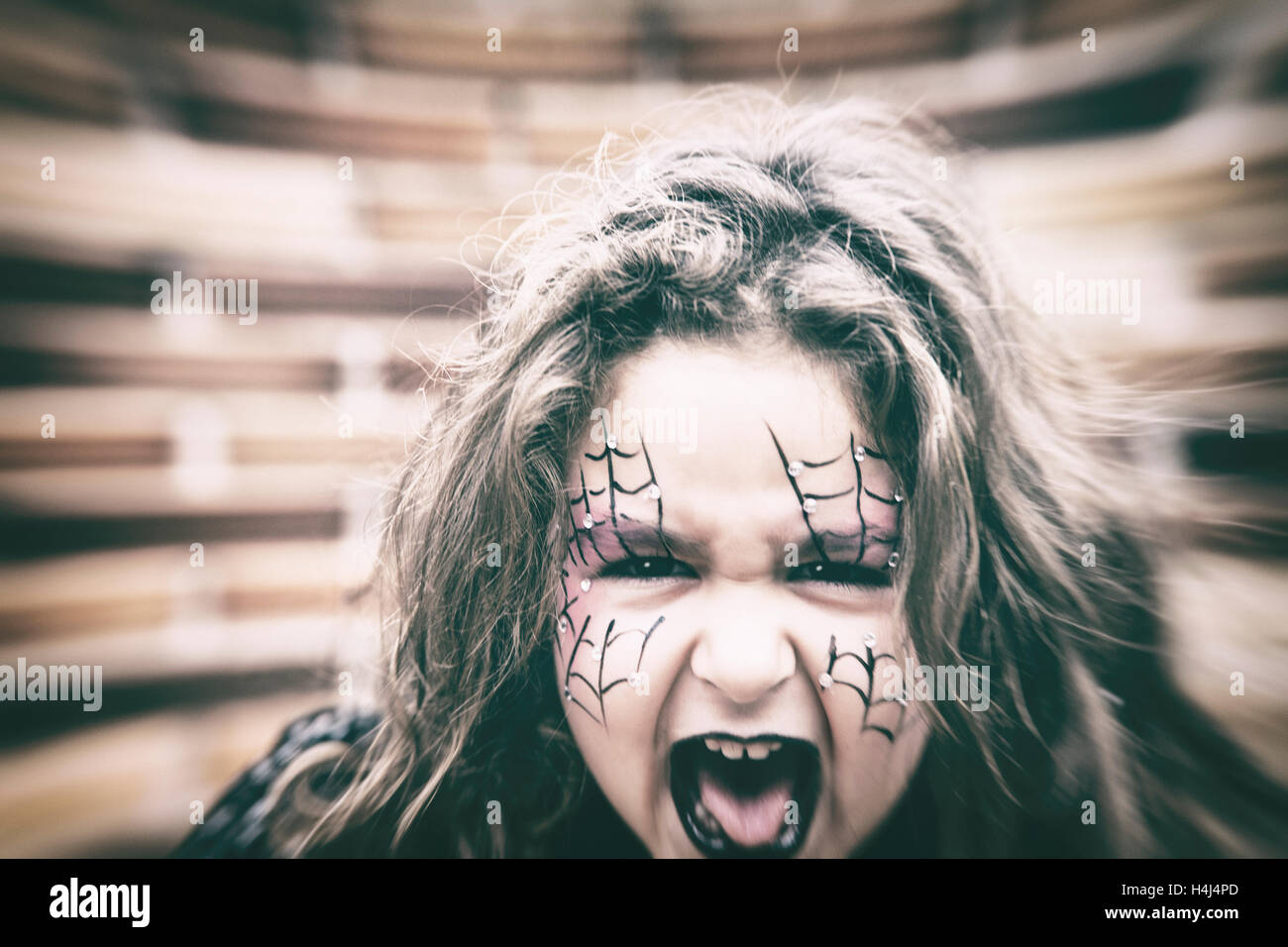 scary little girl in black halloween costume and painted webs on face with open mouth