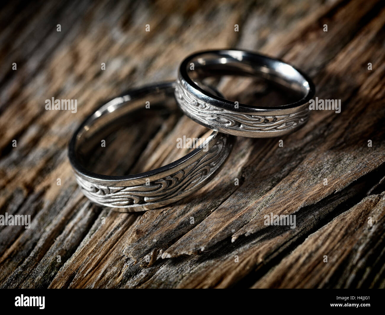 Download this stock image: Two white gold wedding rings with Celtic design on rustic wood background - H4JJG1 from Alamy