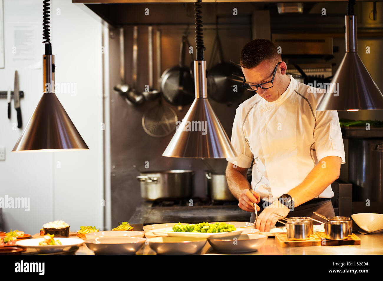 Restaurant Kitchen Chefs chef in a restaurant kitchen, plating food stock photo, royalty