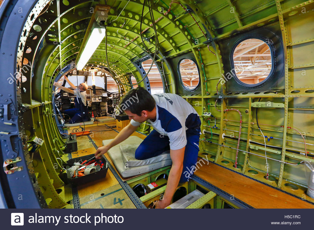 Employees work inside a pilatus pc 12 ng airplane at the for Intranet interior