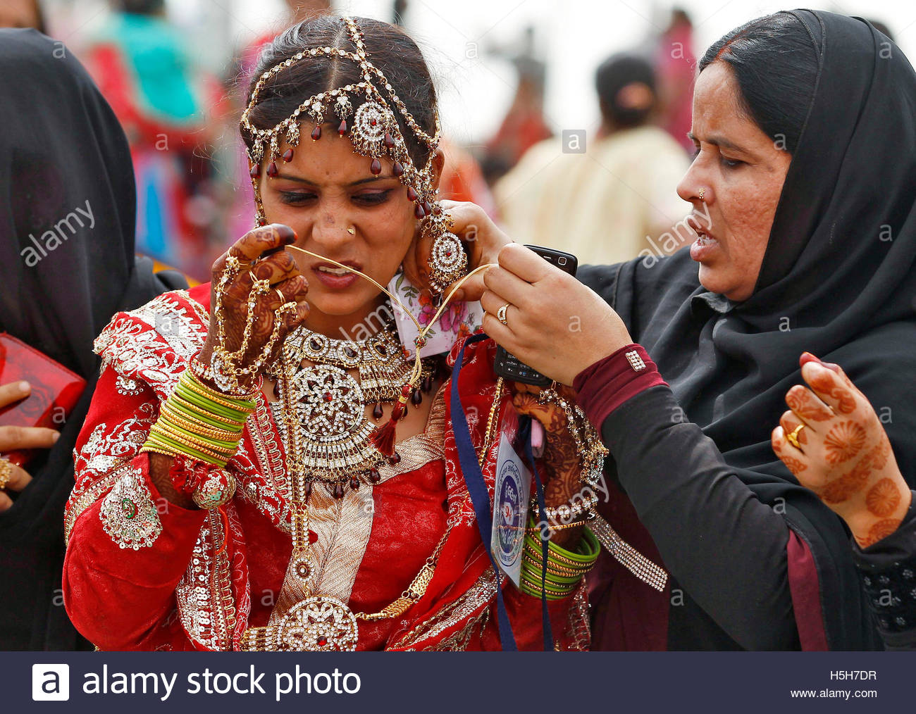 Marriage ornaments - A Muslim Bride Is Helped With Her Ornaments Before The Start Of A Mass Marriage