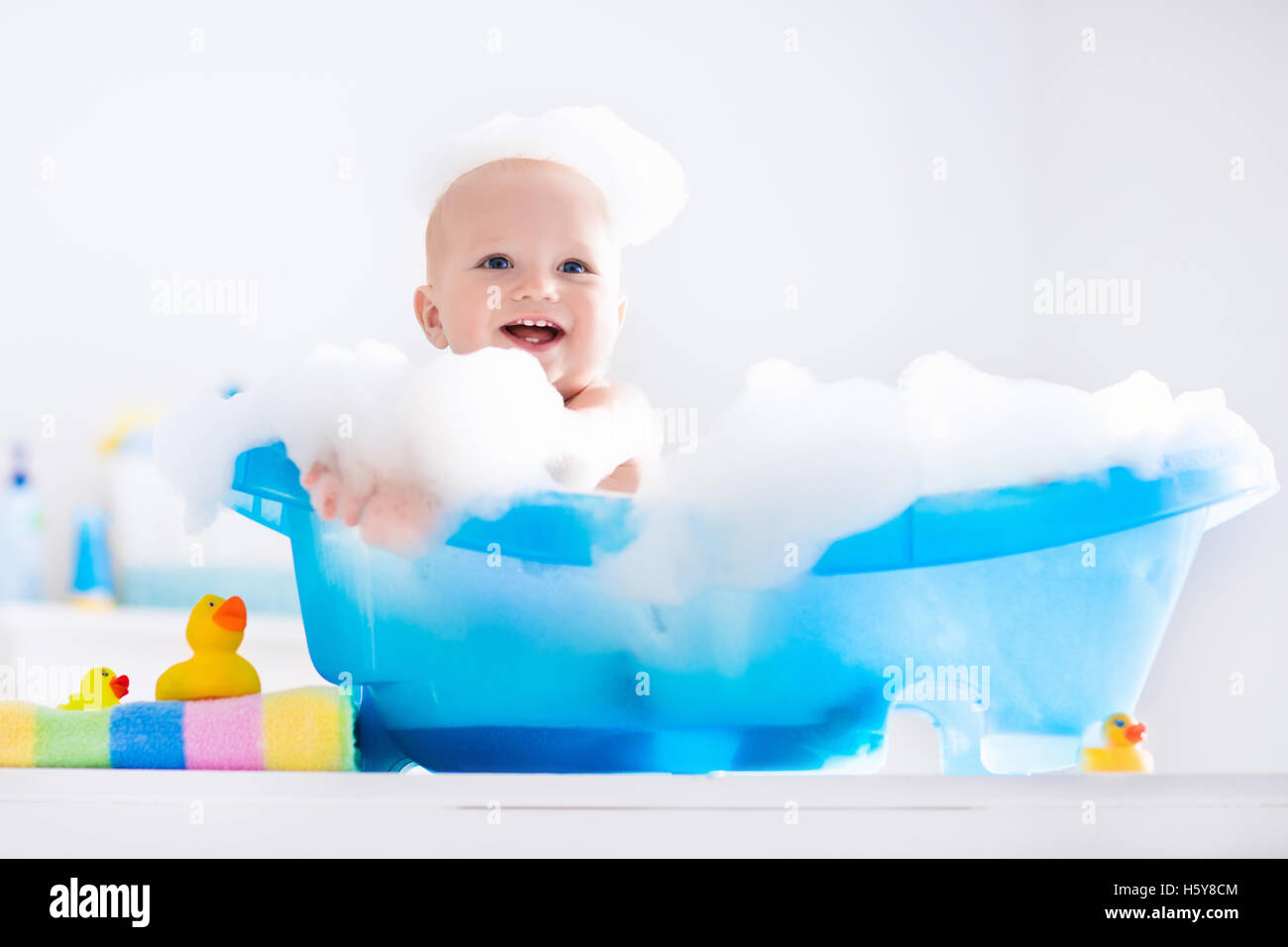 Happy laughing baby taking a bath playing with foam bubbles ...