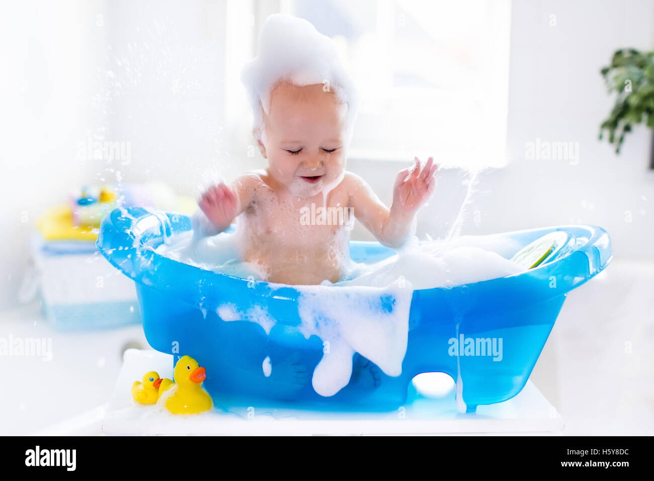 happy laughing baby taking a bath playing with foam bubbles little stock photo royalty free. Black Bedroom Furniture Sets. Home Design Ideas