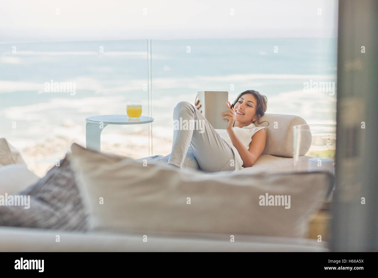 Stock Photo - Woman relaxing reading book on chaise lounge on luxury balcony with ocean vie  sc 1 st  Alamy : reading chaise - Sectionals, Sofas & Couches