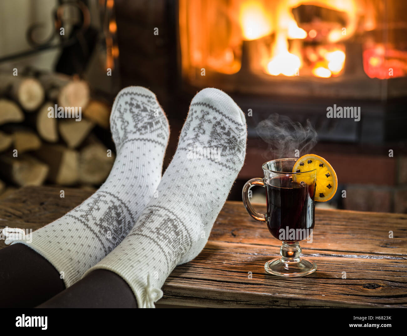 warming and relaxing near fireplace woman feet near the cup of