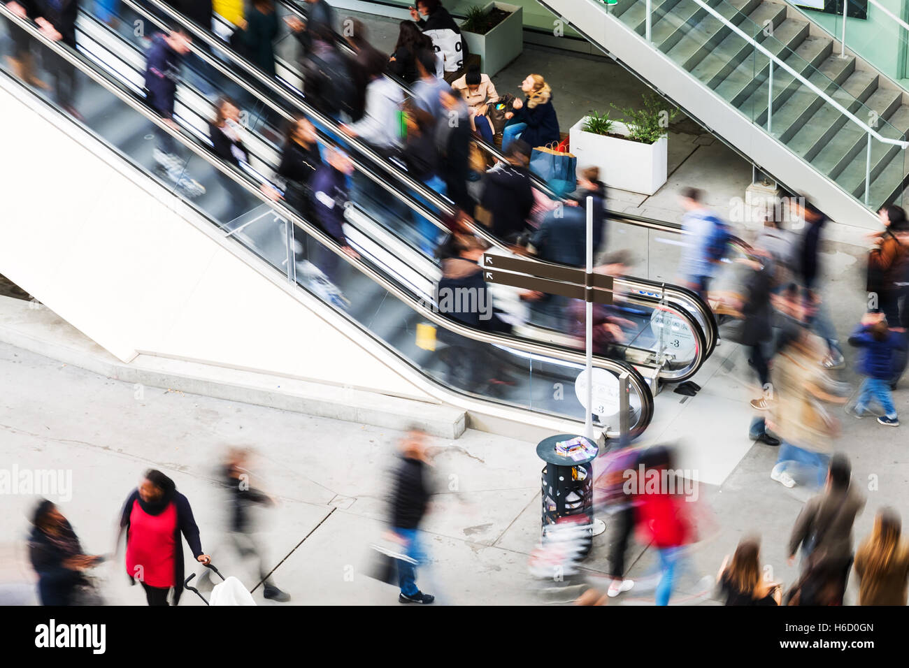 people on escalator. stock photo - escalator with a crowd of people in motion blur at shopping mall on