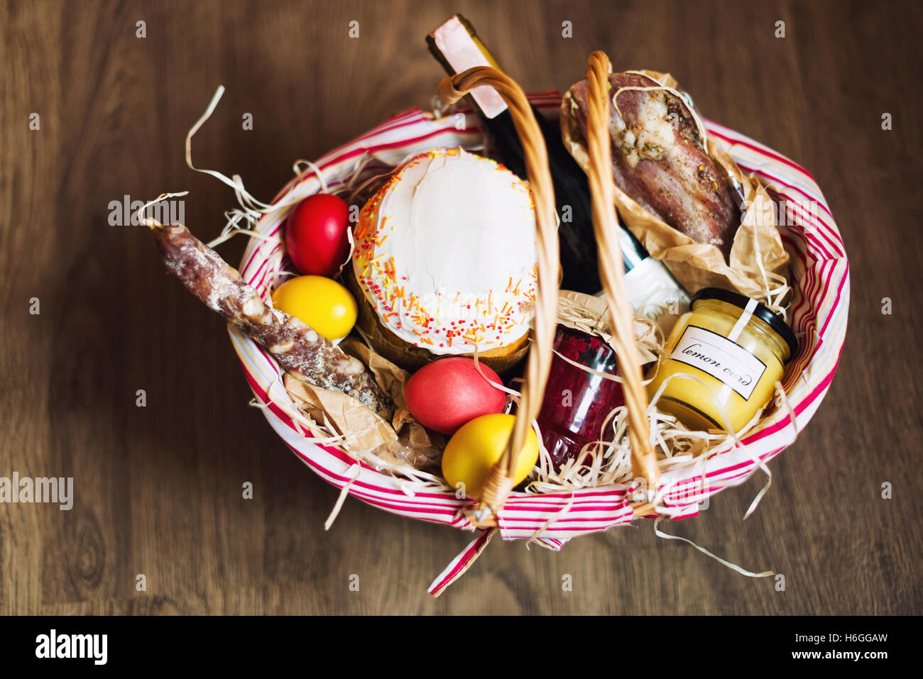Colorful easter eggs in a basket with cake red wine hamon or colorful easter eggs in a basket with cake red wine hamon or jerky and dry smoked sausage on wooden background negle Images