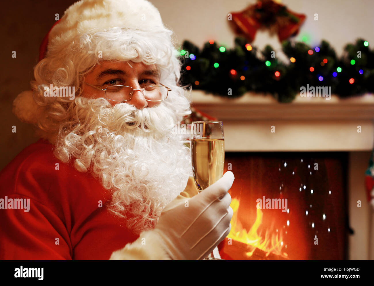 santa claus with glass of sparkling wine champagne near a