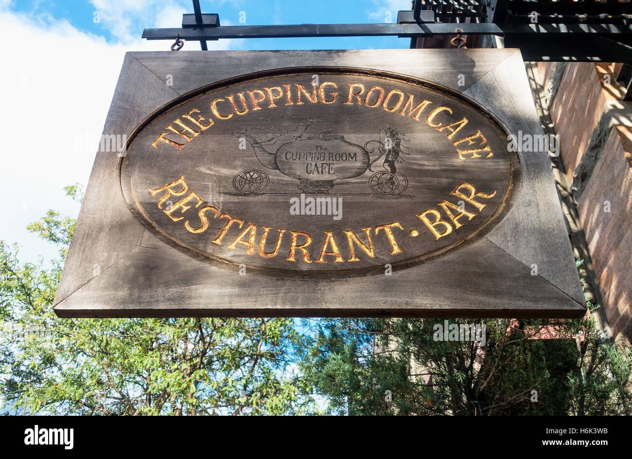 A hanging wooden sign outside The Cupping Room Cafe, a bar ...