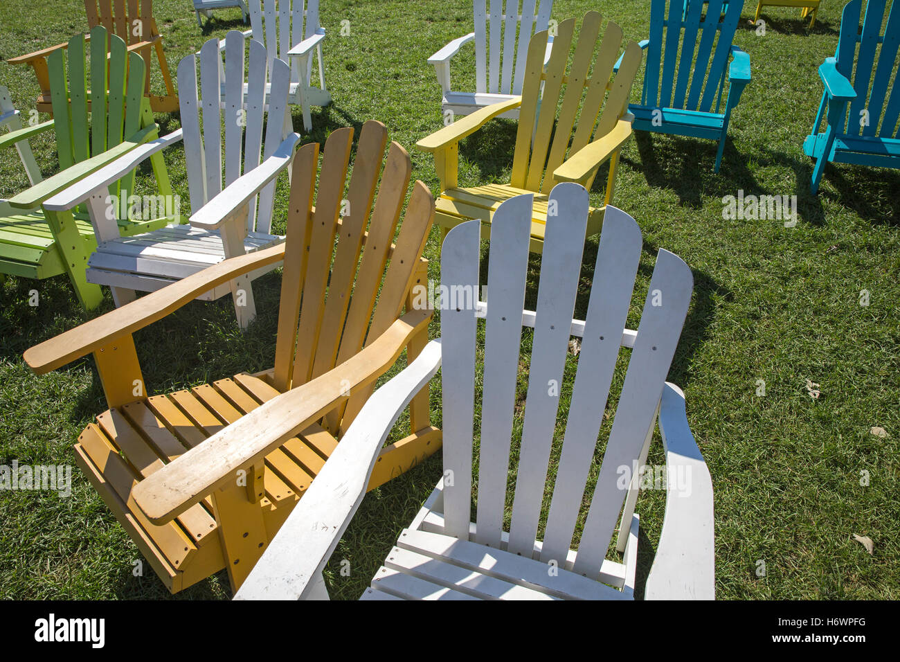 wood deck chairs painted in different colors on grass stock image