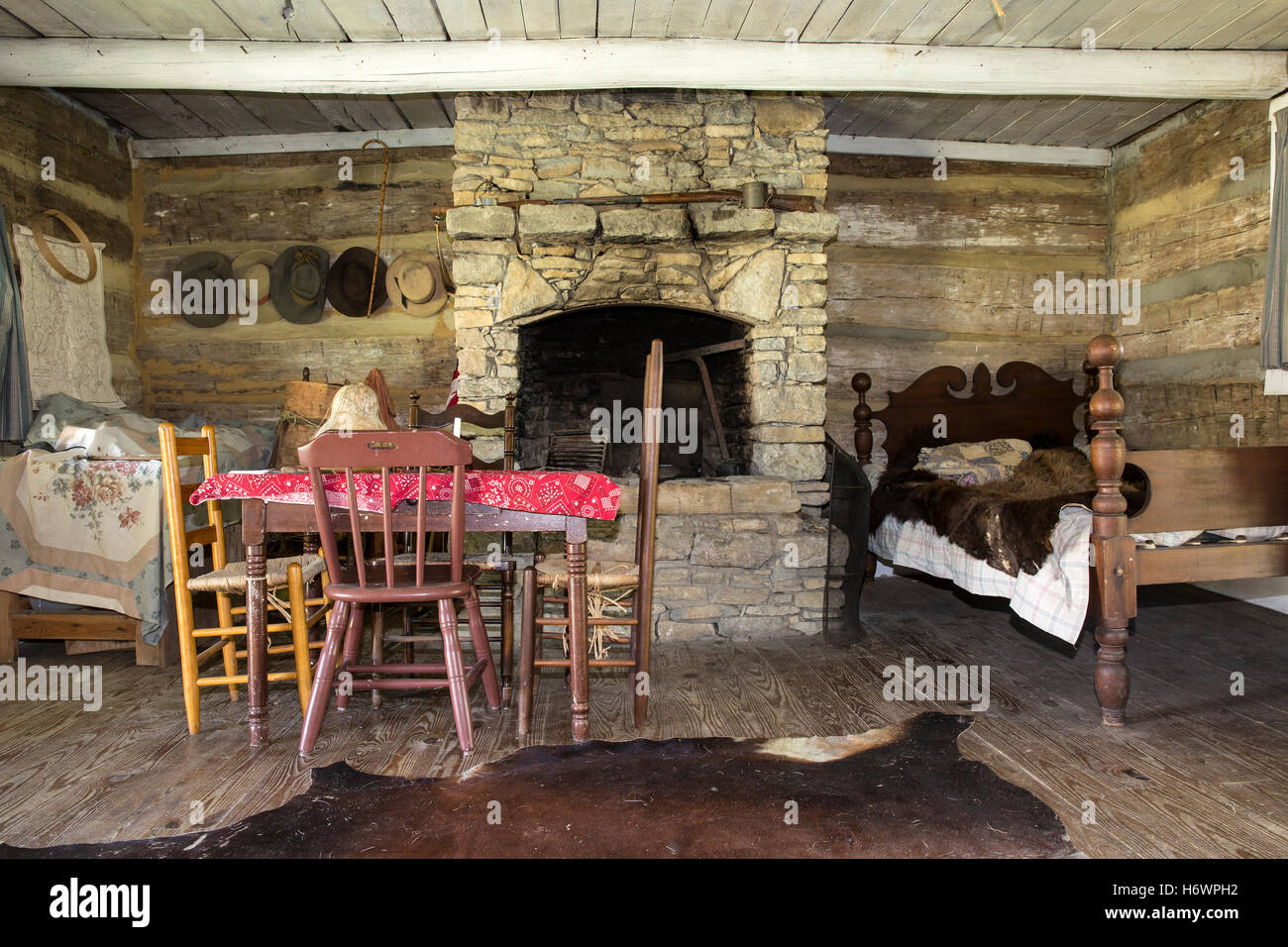 inside of a pioneer cabin with table bed and fireplace caesar