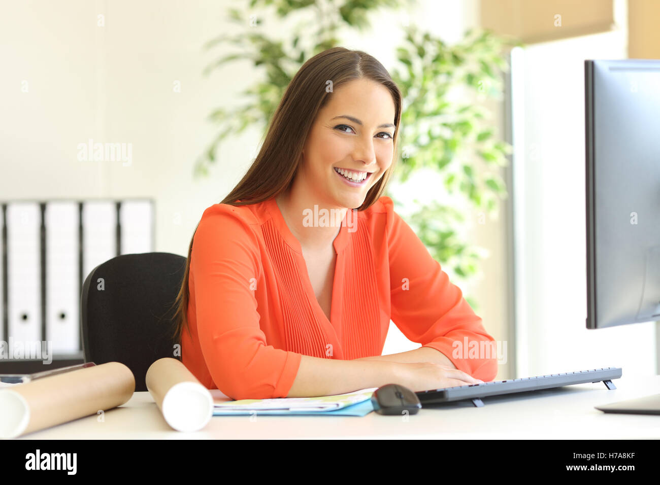 Designer Or Architect Posing And Looking At You Sitting In A Desktop In The  Office With A Window In The Background